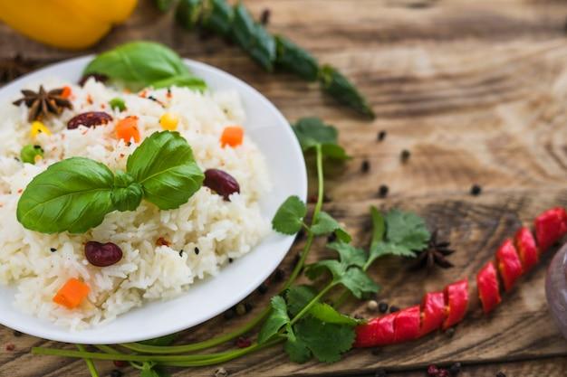 Close-up de arroz saudável; folhas de manjericão; no prato com salsa e pimenta no fundo desfocado Foto gratuita