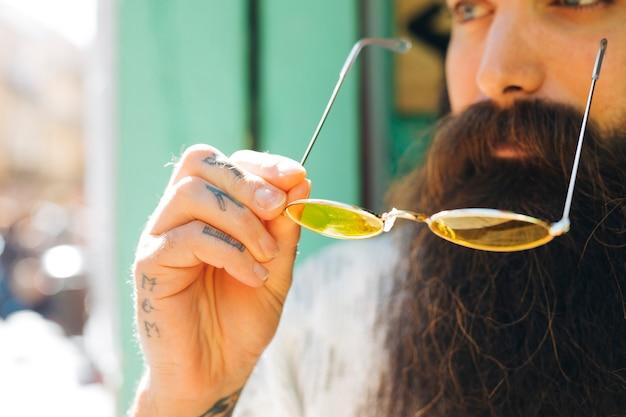 Close-up, de, barba, homem, segurando, amarelo, óculos, em, luz solar Foto gratuita