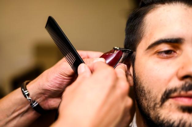 Close-up de barbeiro, dando ao cliente um corte de cabelo Foto gratuita