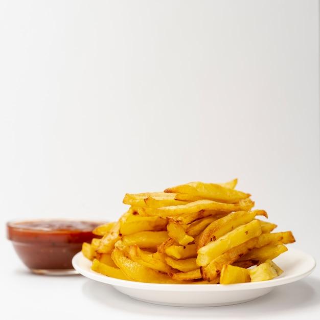 Close-up de batatas fritas com fundo branco Foto gratuita