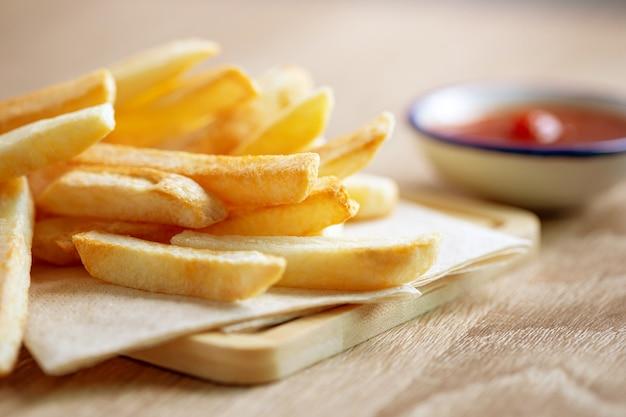 Close-up de batatas fritas com molho de tomate em cima da mesa, junk food insalubre Foto Premium