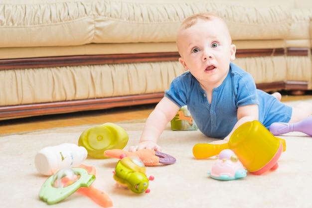 Close-up, de, bebê jogando, com, coloridos, brinquedos, ligado, tapete Foto gratuita