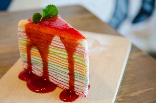 Close-up de bolo de crepe arco-íris na placa de madeira Foto Premium