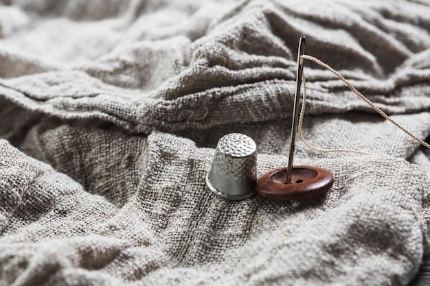 Close-up de botão; dedal; agulha e linha no pano de juta Foto gratuita