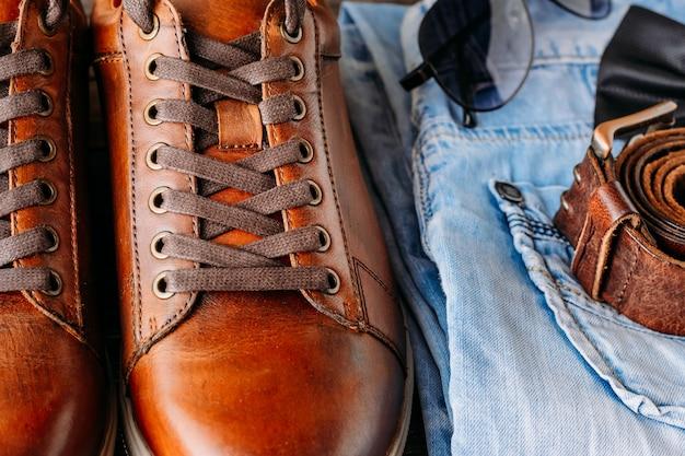 Close-up de botas de couro marrom masculino, cinto, óculos de sol e jeans azul Foto Premium