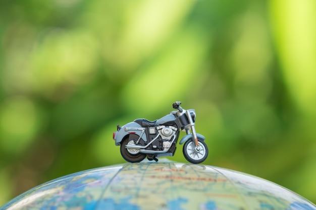 Close-up de brinquedo de motocicleta em miniatura no mapa de balão do mundo Foto Premium
