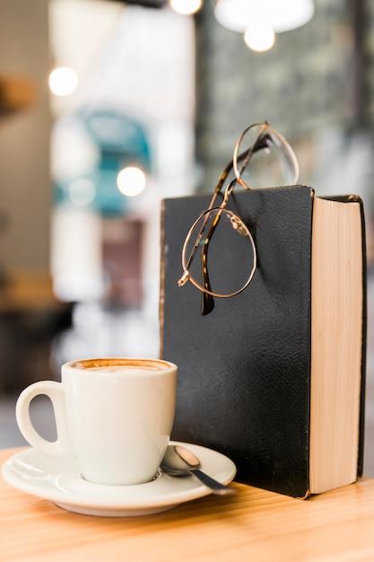 Close-up, de, café, com, espetáculos, e, livro, ligado, escrivaninha madeira Foto gratuita