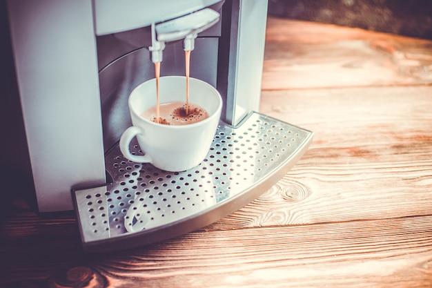 Close-up, de, café expresso, despejar, de, máquina caseiro, cozinhar, toned Foto Premium