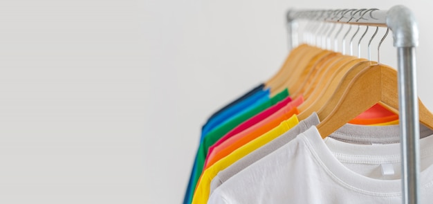 Close-up de camisetas coloridas em cabides Foto Premium