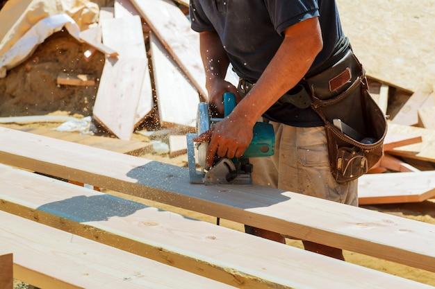 Close-up, de, carpinteiro, usando, um, circular, serra, para, corte, um, grande, tábua madeira Foto Premium