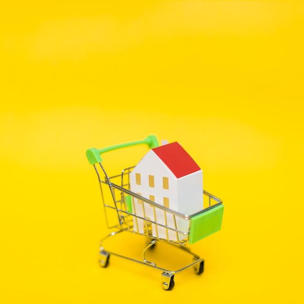 Close-up, de, casa, modelo, em, a, miniatura, carrinho de compras, contra, amarela, fundo Foto gratuita