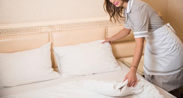 Close-up, de, chambermaid, cama branca, folha, em, sala Foto gratuita