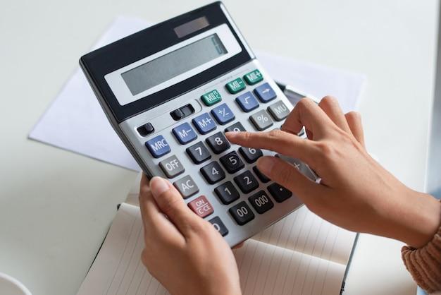 Close-up, de, contador, usando, calculadora, enquanto, examinando, relatório Foto gratuita