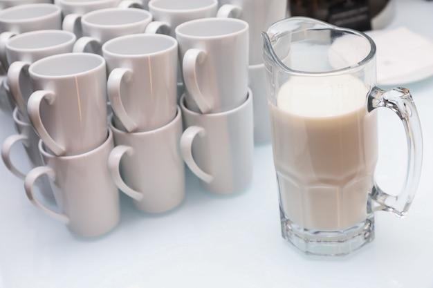 Close-up de copos brancos e um jarro de leite em uma mesa de luz Foto Premium