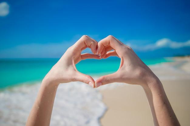 Close up de coração feito por mãos femininas na praia Foto Premium