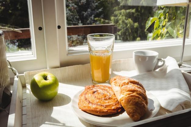 Close-up de croissant e copo de suco em uma bandeja Foto Premium