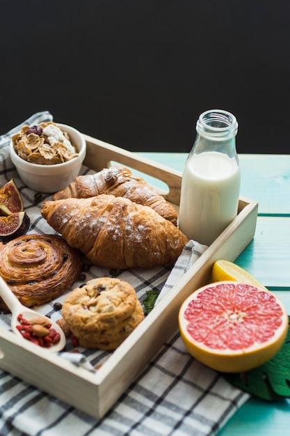 Close-up de croissant fresco; cookies com suporte; leite; muesli; e frutas cítricas com pano em recipiente de madeira Foto gratuita