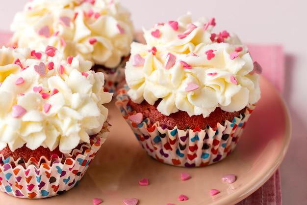 Close-up de cupcakes com granulado em forma de coração e glacê Foto gratuita