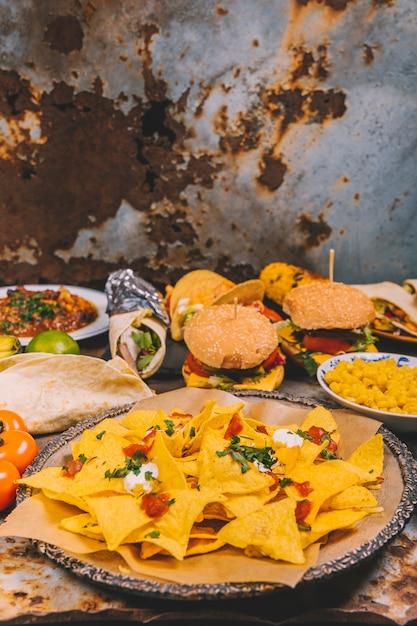 Close-up de deliciosos nachos mexicanos; hambúrguer; milho; tacos de tomate e carne mexicana Foto gratuita