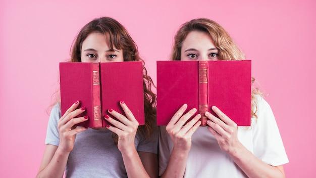 Close-up, de, dois, femininas, amigos, segurando, livro, sob, seu, olhos, contra, fundo cor-de-rosa Foto gratuita