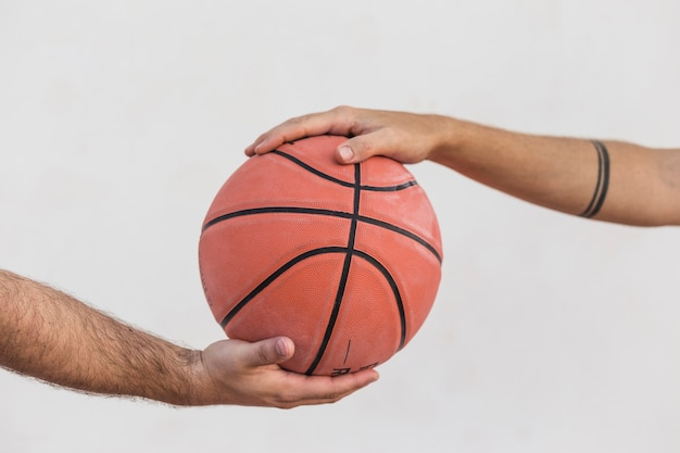 Close-up, de, dois homens, segurando basquetebol Foto gratuita