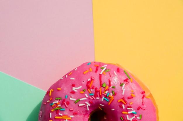 Close-up de donut com polvilha contra amarelo; rosa; e pano de fundo verde menta Foto gratuita