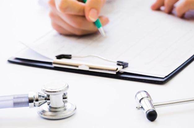Close-up, de, doutor, mão segura caneta, verificar, a, relatório médico, ligado, área de transferência Foto gratuita