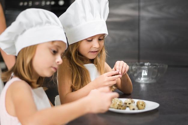 Close-up, de, duas meninas, em, chapéu cozinheiro, peeling, codorniz, ovos, em, prato, casa Foto gratuita
