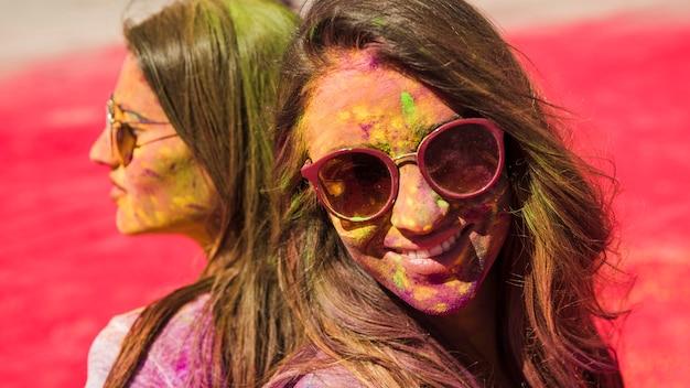 Close-up, de, duas mulheres, desgastar, óculos de sol, coberto, com, holi, cor, pó Foto gratuita