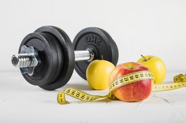 Close-up, de, dumbbells, e, frutas, com, medindo fita, branco, fundo Foto gratuita