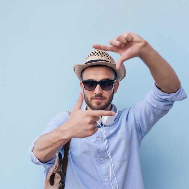Close-up, de, elegante, homem jovem, fazendo, quadro mão, contra, parede azul Foto gratuita