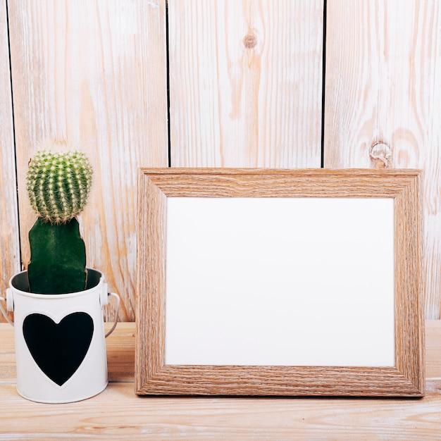Close-up, de, em branco, armação foto, e, suculento, planta, com, heartshape, ligado, pote Foto gratuita