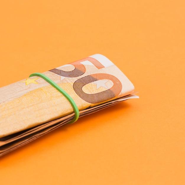 Close-up, de, enrolado, nota euro, amarrada, com, borracha, ligado, um, laranja, fundo Foto gratuita