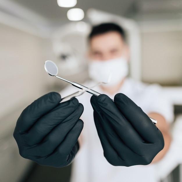 Close-up de equipamento cirúrgico realizado com luvas Foto gratuita