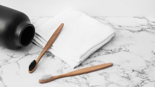 Close-up de escova de dentes de madeira; toalhas brancas e jar na mesa de tampo de mármore Foto gratuita