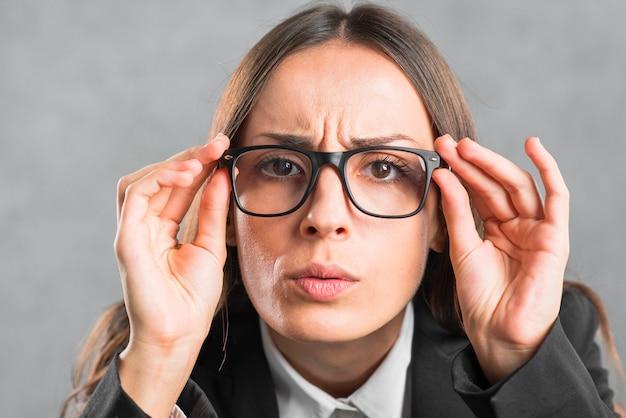 Close-up, de, executiva, olhar, curiosamente, através, pretas, óculos Foto gratuita