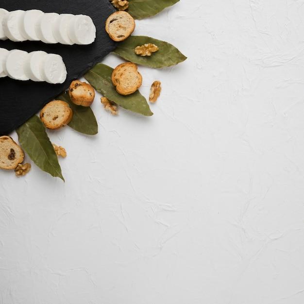 Close-up de fatia de queijo de cabra na ardósia preta com fatia de pão; noz e folhas de louro Foto gratuita