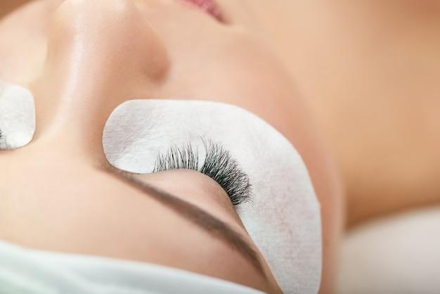 Close-up de fazer o procedimento de cílios longos falsos. Foto Premium