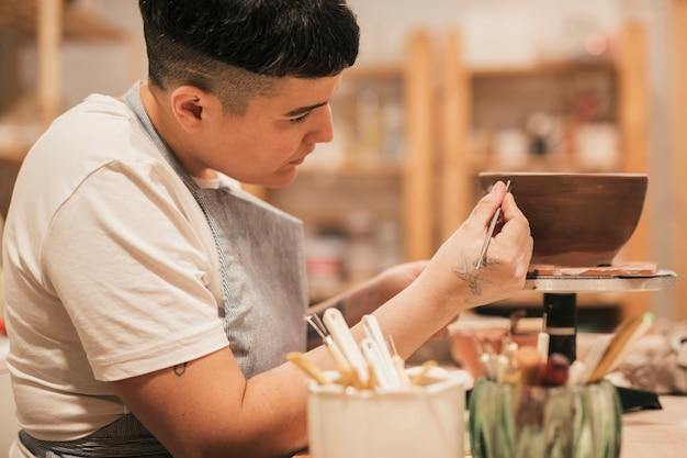 Close-up, de, femininas, mão, quadro, ligado, a, tigela cerâmica, com, ferramentas Foto gratuita