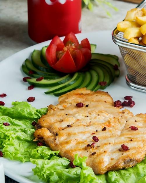 Close-up de filé de peixe grelhado servido com decoração de pepino e tomate Foto gratuita