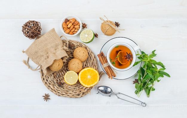 Close-up de frutas cítricas e biscoitos em um jogo de mesa de vime com chá de ervas e coador de chá, Foto gratuita