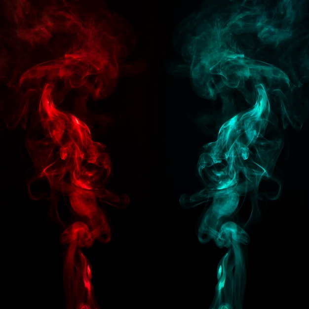 Close-up de fumaça vermelha e turquesa se move em fundo preto Foto gratuita