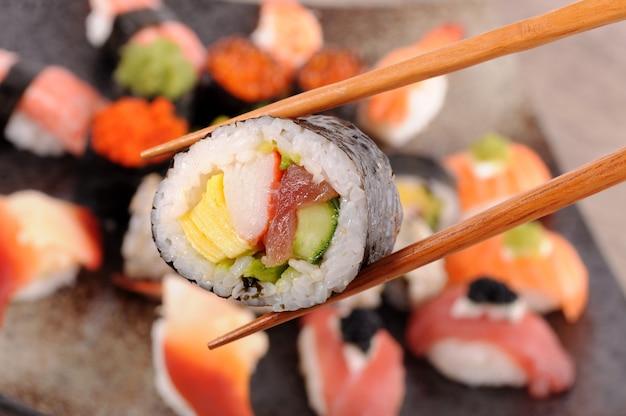 Close-up de futomaki com pauzinhos Foto gratuita