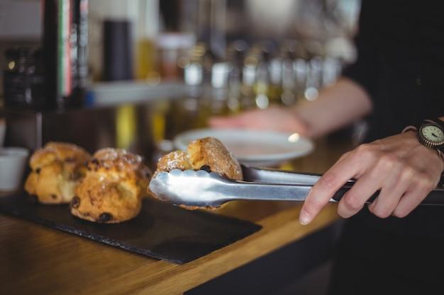 Close-up, de, garçonete, servindo, muffin, em, um, prato, em, contador Foto gratuita