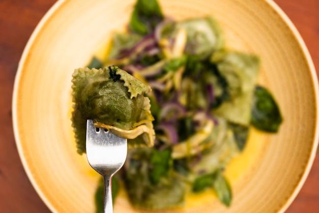 Close-up, de, garfo, com, verde, ravioli, macarronada, em, prato Foto gratuita