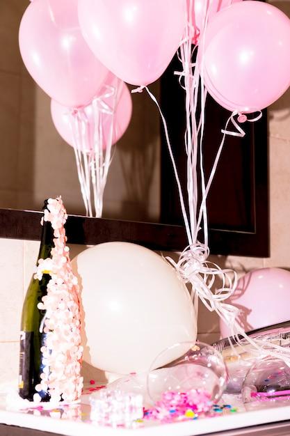 Close-up, de, garrafa champanha, com, confetti, e, cor-de-rosa, balões, escrivaninha Foto gratuita