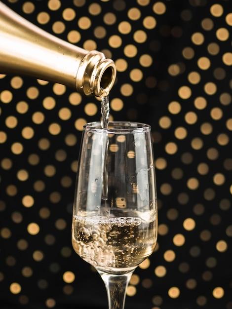 Close-up de garrafa de champanhe derramando em vidro Foto gratuita