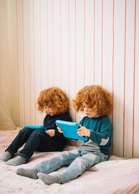 Close-up de gêmeos com cabelo vermelho indo para tablet digital Foto gratuita