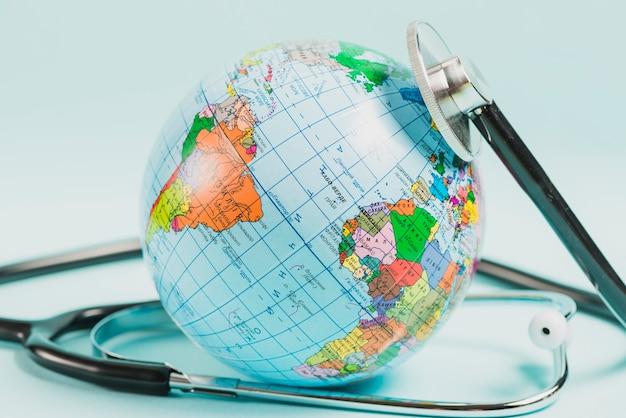 Close-up, de, globo, com, estetoscópio, contra, azul, fundo Foto gratuita