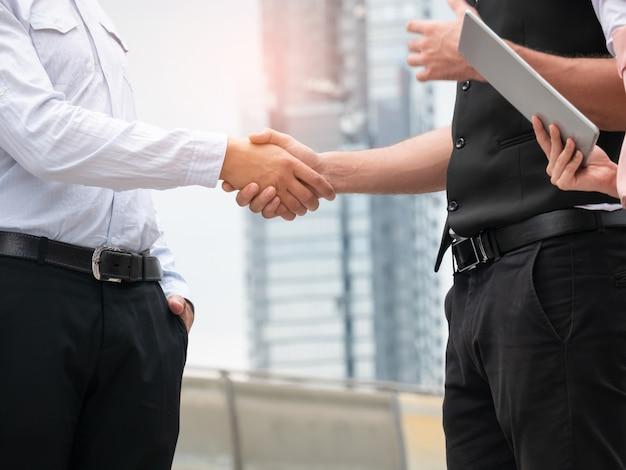 Close-up de handshaking de pessoas de negócios sobre fundo de cidade. reunião ao ar livre de parceria de negócios Foto Premium
